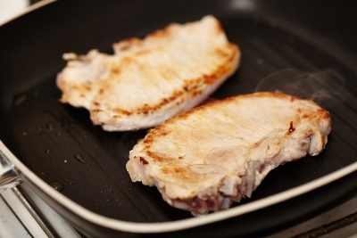 Fried pork chops in the frying pan