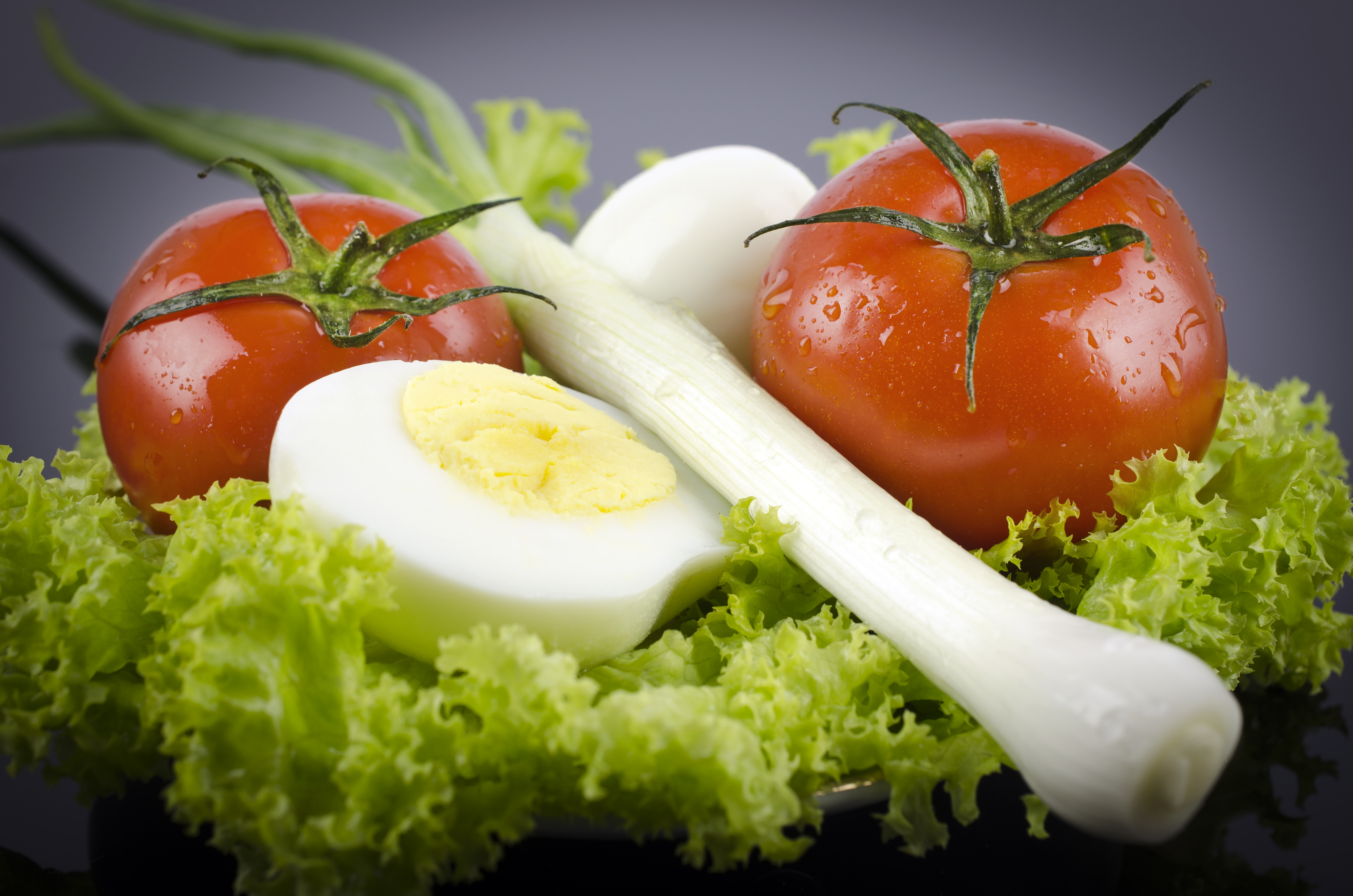 Fresh lettuce, boiled egg tomato, onions on a black table
